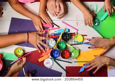 Art supplies in big and tiny hands on white wooden background top view. Artists hands with stationery and colored paper. Creativity and art concept. Hands hold colorful markers pencils and paints