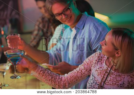 selective focus of friends with drinks looking at each other at counter in bar