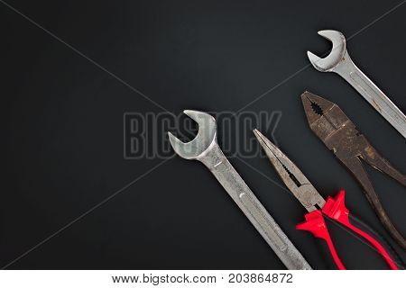 Must have at home used hand tools Combination Pliers, Needle Nose Pliers, wrench on black background with copy space