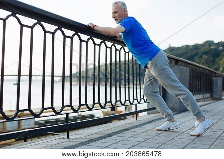 Healthy lifestyle. Athletic senior man leaning on the balustrade and performing stretching during his morning run