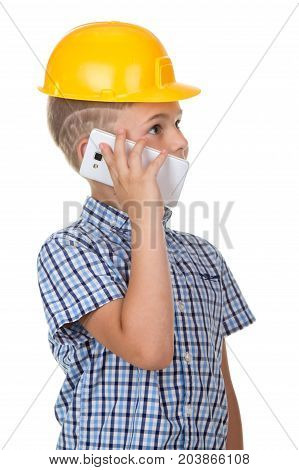 Cute builder boy speaks by phone, wearing yellow protectie helmet and blue checkered shirt. White background