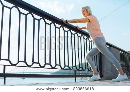 Improving suppleness. Athletic slender senior woman resting her hands on the balustrade and warming up before a morning run by doing stretching