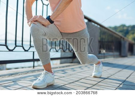 Preparation for running. The close up of a fit senior woman doing lunges on the bridge while getting ready for her morning run
