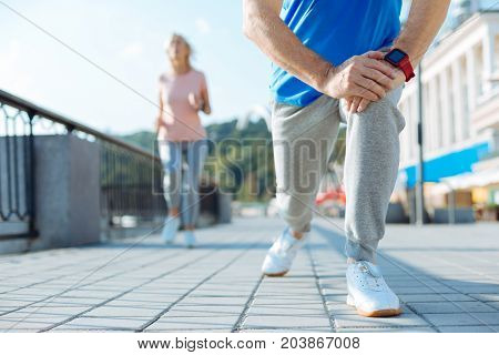 Important exercises. The close up of a fit senior man doing lunges in the street, warming up before his morning run, while a woman jogging in the background