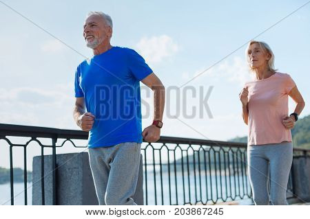 Upbeat mood. Cheerful energetic senior couple running down the bridge and smiling happily while having their morning exercises