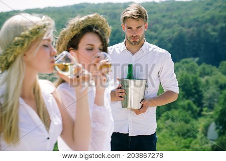Macho or man with champagne bucket. Blur girls or women drinking white wine. Winery tour and picnic. Summer vacation concept. Friends enjoying alcohol on natural landscape.