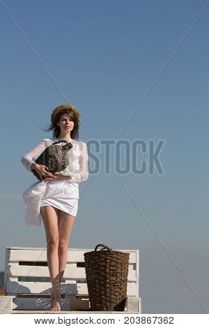 Girl in white dress and wreath on blue sky. Summer vacation holidays and celebration. Harvesting and winemaking. Winery tour concept. Woman with wicker bottle and basket standing on bench copy space