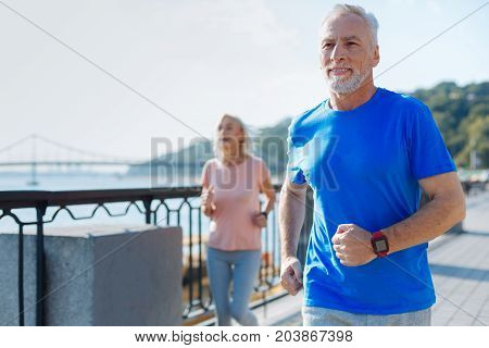 Exercising together. Pleasant senior man jogging down the bridge together with his beloved wife jogging slightly behind him