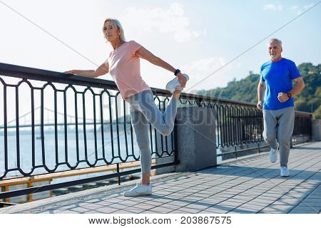 Everyday routine. Athletic elderly lady holding on to the bridge balustrade and doing stretching exercises while a senior man jogging down the bridge