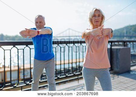 Careful preparation. Lovable elderly couple stretching hands and back while doing a warm-up before jogging.
