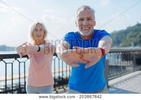 Preliminary warm-up. Pleasant elderly couple working out together in the streets, holding hands in a lock and performing stretches