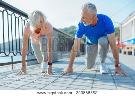 Starting together. Pleasant upbeat elderly couple standing in the starting position, being ready to start the race