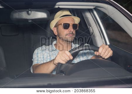 Portrait of young man on driver seat wearing hat and sunglasses. On the road and travel concepts.