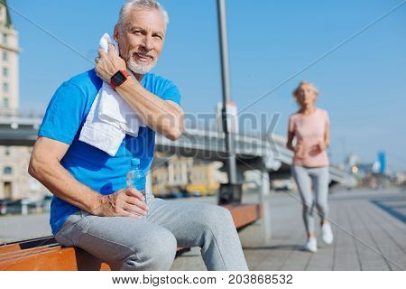 Well-deserved rest. Handsome pleasant senior man sitting on the bench, wiping the sweat with towel, resting after a workout while a woman jogging in the background