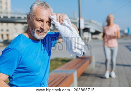 Getting some rest. Handsome senior man sitting on the bench and wiping sweat from the forehead with towel after a morning run while a woman running in the background