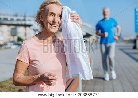 Sport brings happiness. Pleasant happy elderly woman sitting on the bench, wiping sweat from her forehead with towel and smiling happily while a man jogging in the background