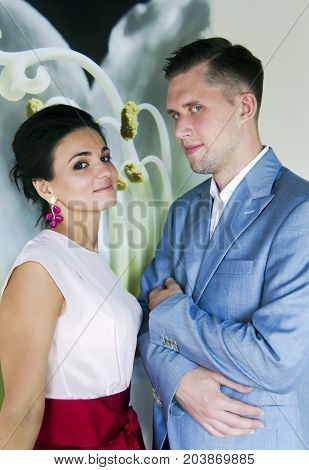 Happy young couple: man in elegant blue suit, women - silk blouse, beautiful make-up and hairstyle together they look at the camera in Riga, Latvia
