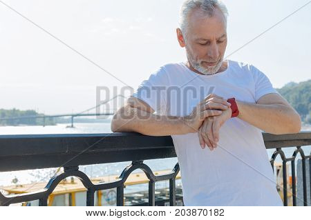 In anticipation. Handsome elderly man leaning on the balustrade of the bridge and looking at his smart watch, checking time while waiting for someone