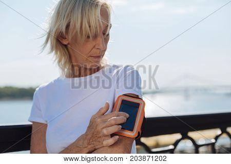 Convenient device. Fit elderly woman wearing an arm band for smartphones and pressing the touchscreen of her phone, tracking the distance of her morning run