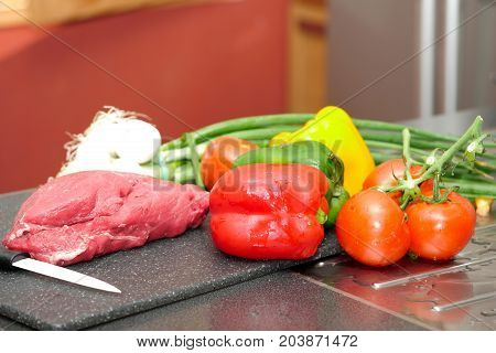 a piece of raw meat with vegetables