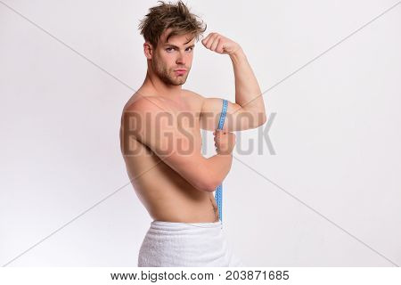Athlete With Messy Hair Measures Muscles. Measurement And Sports