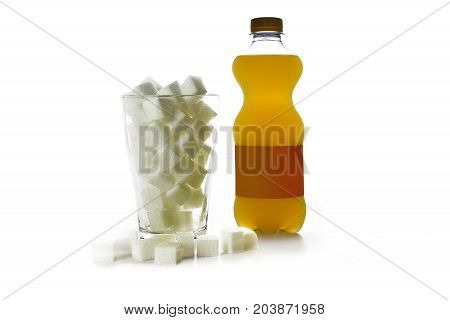 Bottle of orange sweet drink and a glass full of sugar cubes concept for unhealthy beverages isolated on a white background