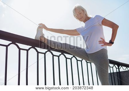 Impressive results. Slender senior lady holding her leg on the top of a bridge balustrade and performing stretching exercises, demonstrating excellent results in it