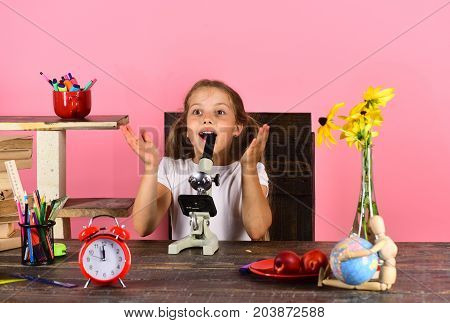 Kid And School Supplies On Pink Background. Schoolgirl At Desk