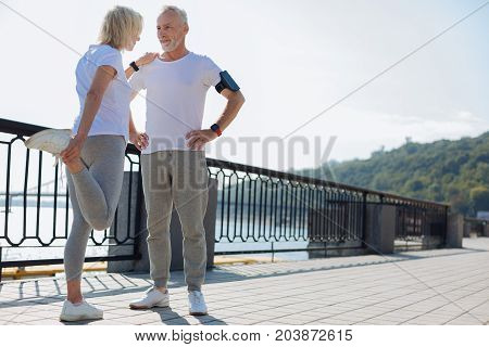 I will help. Fit senior man standing in the street and providing balance for his wife doing stretching exercises and leaning on his shoulder for support