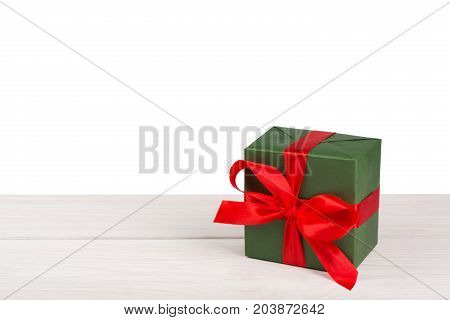 Gift box wrapped with green paper and red satin ribbon on wood at white background. Modern presents for any holiday, christmas, valentine or birthday