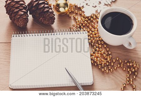 Christmas planning background. Prepare to winter holidays mockup. Xmas decorations, note papers, pen, coffee on wood. Copy space for wishlist or shedule