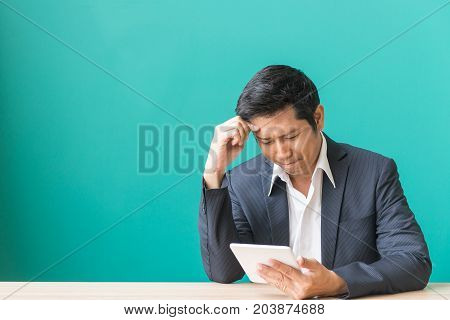 Front view. Young bearded sad businessman is sitting at table covering his face with his hand and holding smartphone in his hand. On desk is laptop tablet computer. Man got bad news. Stressed.