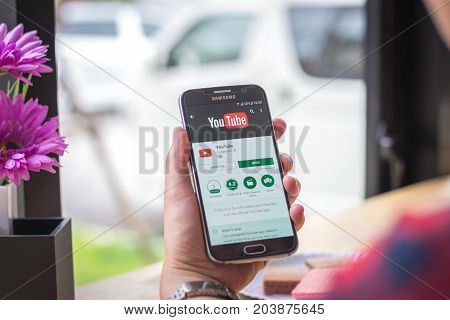 Chiang Mai, Thailand - September 12, 2017: Samsung Galaxy S6 smartphone launches youtube music application on the desk screen at the coffee shop.