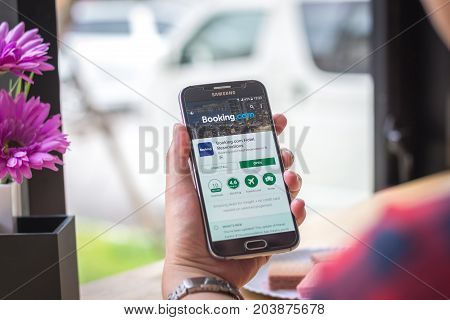 Chiang Mai, Thailand - September 12, 2017: Samsung Galaxy S6 smartphone launches booking com application on the desk screen at the coffee shop.
