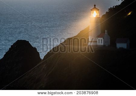 The Light of Heceta Head Lighthouse Shines at Dusk along the Oregon coast