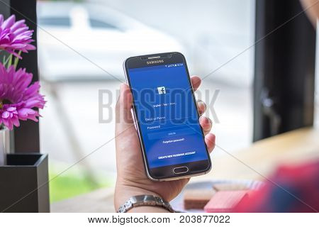 Chiang Mai, Thailand - September 12, 2017: Samsung Galaxy S6 smartphone launches faceebook application on the desk screen at the coffee shop.
