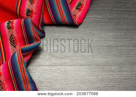 Color vibrant pattern tablecloth on wooden table for background. Fabric texture. Wooden texture.Template for designers