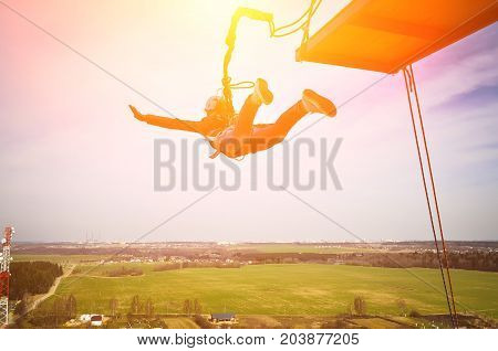 Rope jumping or bungee jumping, girl jumping to the bottom, extreme background