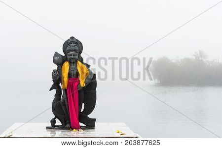 Hindu staue in a temple (Grand Basin) in the day with mist create mystical atmosphere.Mauritius