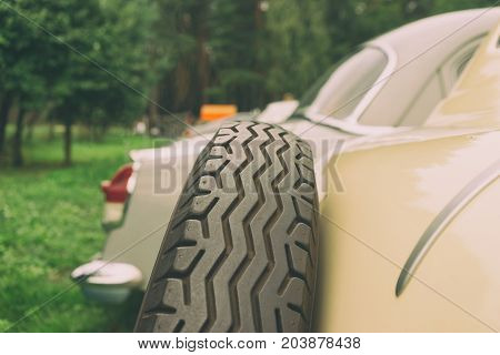 A wheel with a zigzag protector on the trunk of a vintage car in a green forest