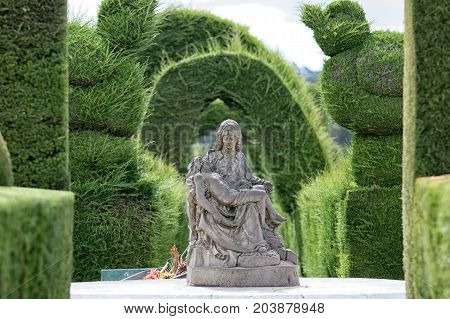 May 16 2017 Tulcan Ecuador: religious statue surrounded by green topiary in the famous cemetery