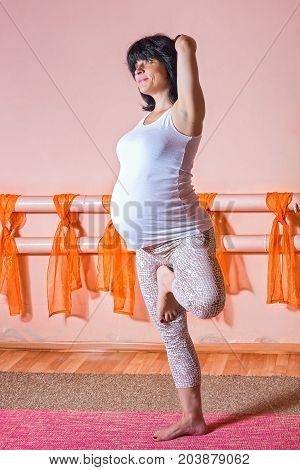 Healthy lifestyle maternity concept. 40 week pregnant middle aged caucasian woman standing on the one leg in asana doing yoga exercises with her arms in gomukasana asana.