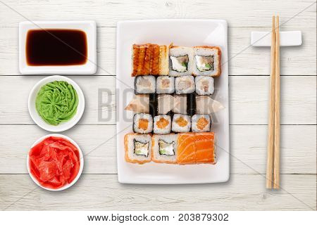 Japanese food restaurant delivery - sushi maki, unagi and roll platter set isolated on white wood background, above view
