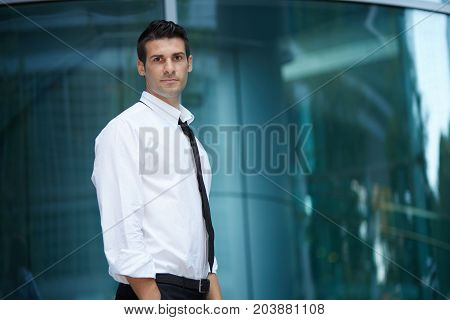 young handsome businessman standing outside office building