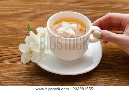 Female Hand And A White Mug Of Tea With Jasmine On A Wooden Table. Close-up