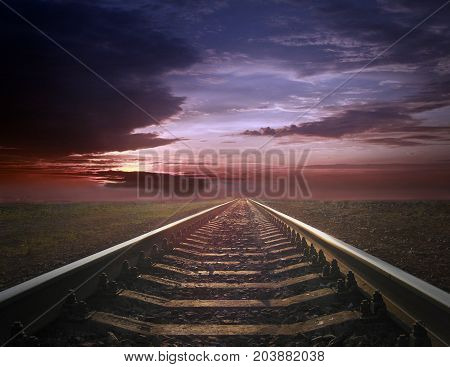 rails going away into the gloomy landscape. Black and white image with rails going away into the dark sky landscape