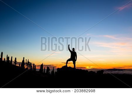Man celebrating sunset in mountains with arms outstretched. Trail runner hiker or climber with hands raised reached a goal on top of a mountain enjoying inspirational landscape on rocky trail Tenerife Canary Islands