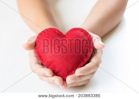 Red felt heart in childs hands on white background. View from above. Copy space.