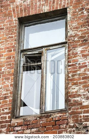 Broken window in an old house of red brick