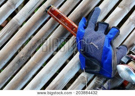 fishing rod reel blue glove and black bait lure on bamboo background